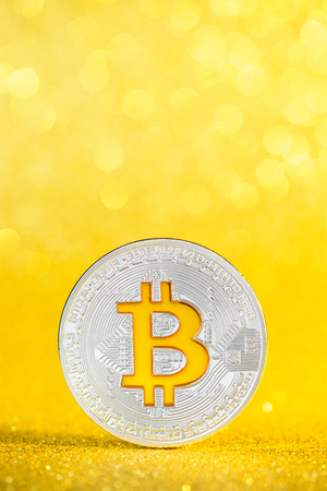Bitcoin coin with golden bitcoin symbol on golden glitter bokeh background