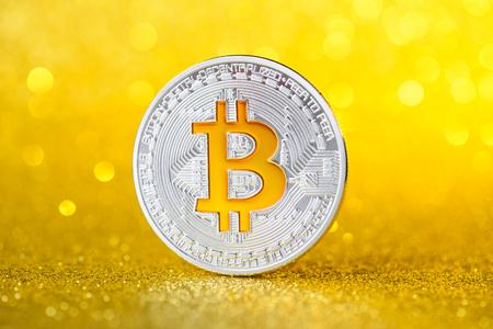 Shiny silver bitcoin coin. Golden bitcoin symbol on golden shiny glitter background