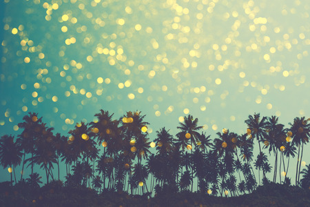 Palm trees on tropical beach, vintage toned and retro color stylized with shiny golden party bokeh background