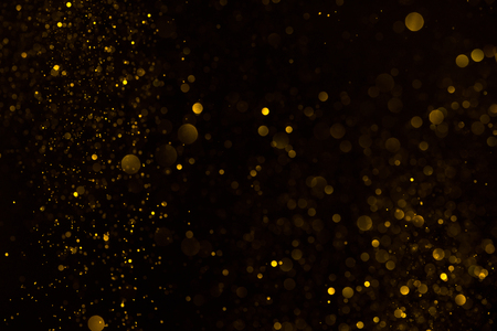 Gold glitter falling sparkle background on black