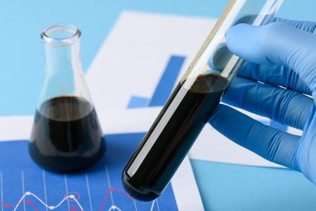 Prueba de laboratorio de petróleo crudo en un vial en la mano del científico. Aceite crudo natural sin tratar.