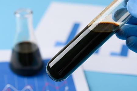 Crude oil in vial test tube in laboratory scientist hand. Foto de archivo