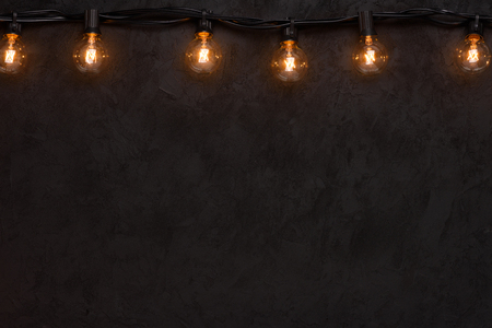 Garlands of lamps border. Warm glass lamps of dark wall with copy space.