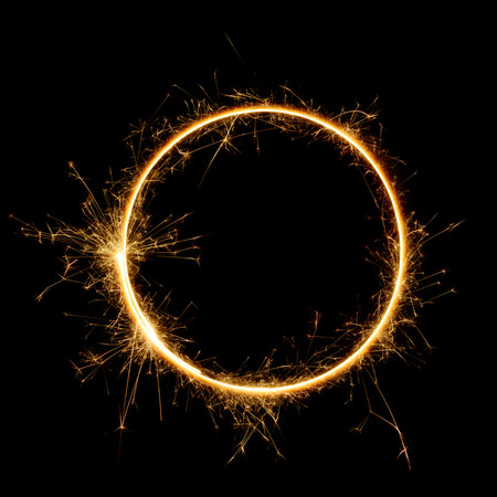 Sparkler circle shape. Burning bengal fire round letter o number zero, long exposure. Burning sparklers isolated on black. Banco de Imagens