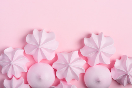 Meringue cookies border. Sweet crispy twisted and drop meringue on pink pastel background with copy-space.