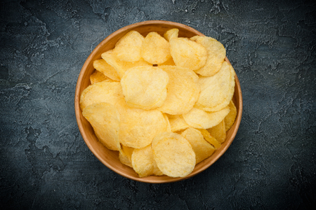 Crispy potato chips fried with olive oil and salted in bowl on dark table