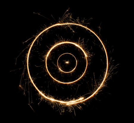 Sparkler concentric circles. Burning bengal fire concentrical round letter o number zero. Isolated on black.
