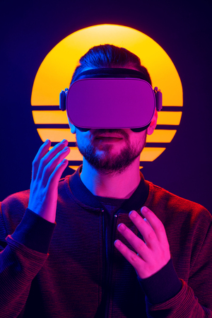 Man wearing virtual reality goggles and interacts with hand gestures. VR head set videogame in 80s synthwave and retrowave futuristic aesthetics.