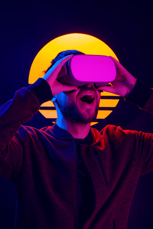Man wearing virtual reality goggles experiencing fun entertainment. VR head set videogame in 80s synthwave and retrowave futuristic aesthetics.