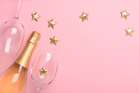 Champagne with glasses and golden stars on pink background
