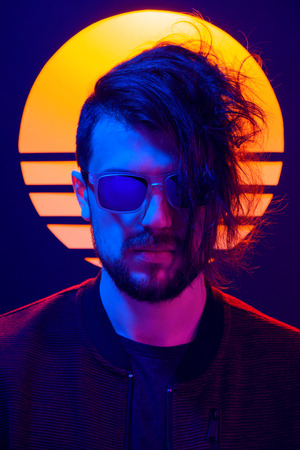 Retro wave synth wave portrait of a young man in sunglasses. 80s sci-fi futuristic fashion poster style violet neon with sun on background.