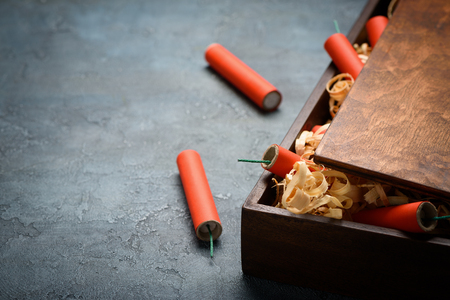 Red dynamite tnt firecrackers fuse in wooden box crate with wooden shavings.