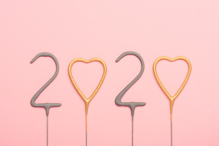 New year 2020 sparklers numbers and golden hearts on pink background