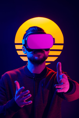 VR video game experience in 80s synth wave and retro wave futuristic aesthetics. Man wearing virtual reality goggles wireless headset and interacting with hand gestures.