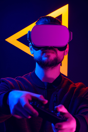 Man wearing virtual reality goggles interacting with VR using game pad wireless controller. VR headset videogame in 80s synth wave and retrowave glowing triangle futuristic aesthetics.