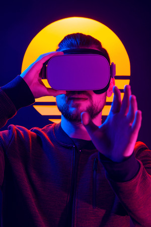 Man wearing virtual reality glasses headset. Vr world experience. Videogame in 80s synthwave and retrowave futuristic aesthetics.