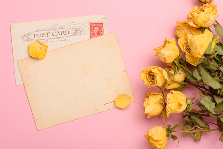 Vintage post cards with dry yellow roses flowers on pastel rose background top view Imagens