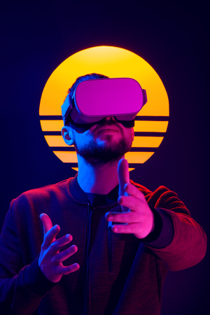 Man wearing virtual reality goggles and interacts video game with hand gestures. VR head set videogame in 80s synth wave and retro wave futuristic aesthetics.