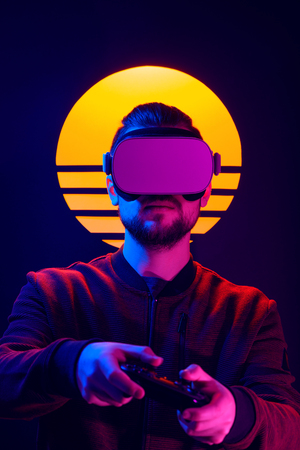 Man wearing virtual reality goggles playing video game with gamepad joystick controller. VR head set videogame in 80s synth wave and retro wave futuristic aesthetics.