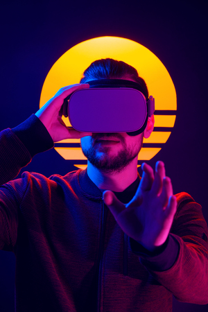 VR videogame experience in 80s synthwave and retrowave futuristic aesthetics. Man wearing virtual reality goggles wireless headset and interacting with hand gestures.
