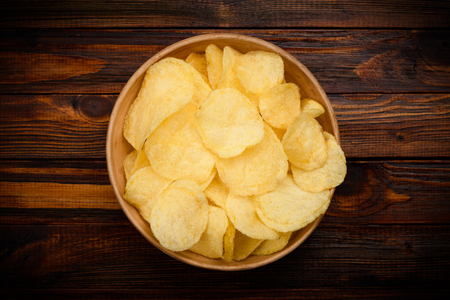 Potato chips in bowl on dark rustic wooden table Imagens