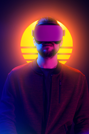 VR head set videogame in 80s synthwave and retrowave futuristic vaporwave aesthetics. Man wearing virtual reality goggles looking straight.
