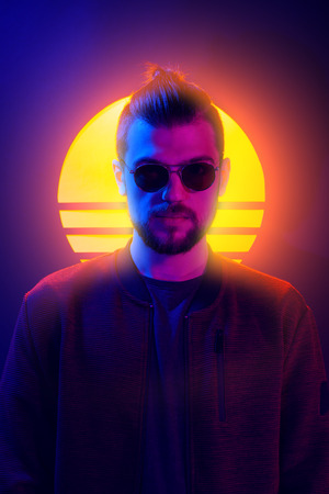 1980s sci-fi futuristic fashion poster style violet neon. Retro wave synth vapor wave portrait of a young man in sunglasses. Imagens
