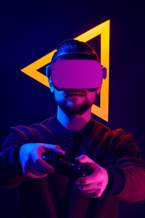 Man playing video game on wireless VR headset. Virtual reality goggles head set videogame in 80s synth wave and retro wave glowing triangle futuristic aesthetics. Imagens