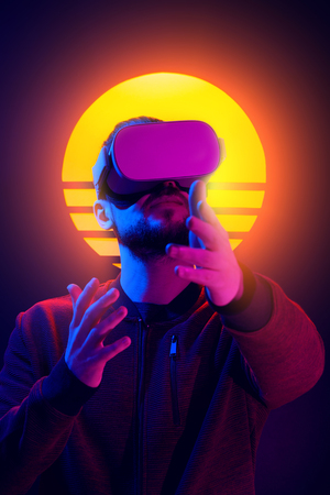 80s synth wave and retro vapor wave futuristic aesthetics. VR video game experience. Man wearing virtual reality goggles wireless headset and interacting with hand gestures. Imagens