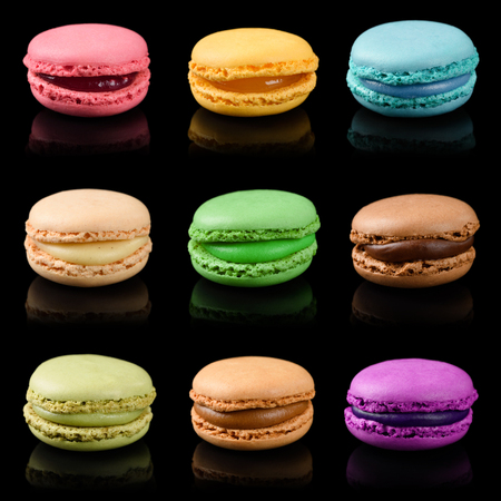 Sweet colorful macarons isolated on black background. French macaroons set.
