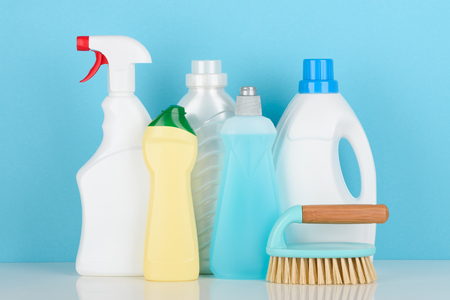 Cleaning liquids and tools set for different housework on white table.