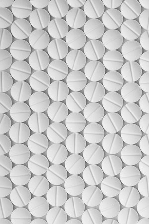 White pills on white background. Tablets pattern macro. Drugs abstract background top view.