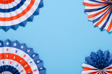 US flag colored paper star fans on blue background.