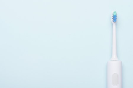 Electric toothbrush. Sonic tooth brush on blue background with copy-space. Stock Photo