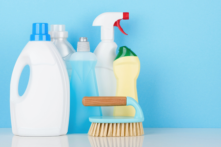 Cleaning product accessories on white table with copy-space.