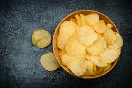 Crispy potato chips in bowl on dark rustic table. Overhead top view with copy space. Reklamní fotografie