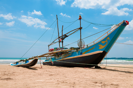Fishing boat with nets on sandy ocean shore in asia.