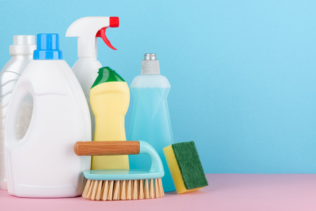 Cleaning liquids and tools set for different housework. Bathroom, kitchen, office house cleaning service equipment on pastel background with copy space. Stock Photo