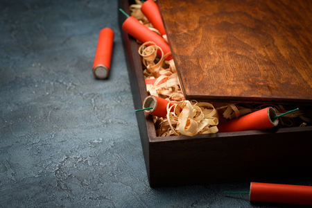 Wooden crate with red dynamite firecracker tnt sticks on table with copy space.