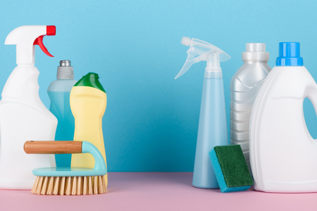 Cleaning liquids and tools set for different housework. Bathroom, kitchen, office house cleaning service equipment on pastel background with copy space in between.