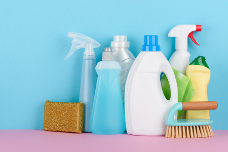 Cleaning products on pastel background. Sanitary supplies accessories assortment.