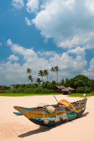 Old fishing boat on the beach with fishermans shed on background at Sri Lanka.