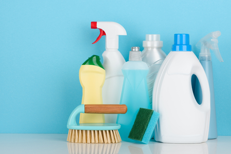 Cleaning liquids assortment and tools set for different housework on white table with copy-space. Stock Photo