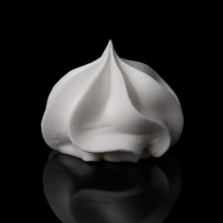 White big meringue cookie isolated on black background with reflection. Stock Photo