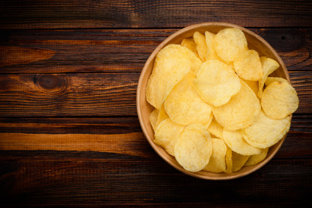 Potato chips in bowl on dark wooden table