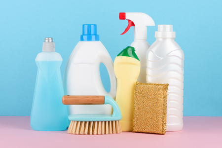 Cleaning supplies assortment. Cleaning brush, plastic bottles with liquids, golden sponge on pink and blue pastel background.