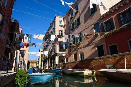 Venice Italy street with laundry washed clothes hanging out to dry on ropes between houses over the canal