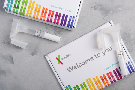 Kiev, Ukraine - 17 October 2018: 23andMe personal genetic test saliva collection kit, with tube and box on table overhead view. Illustrative editorial.