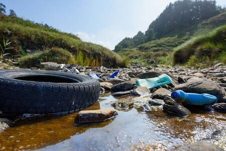 Earth plastics pollution global enviroment emergency. Old car tire in dirty water with plastic bottles and trash.  Stockfoto