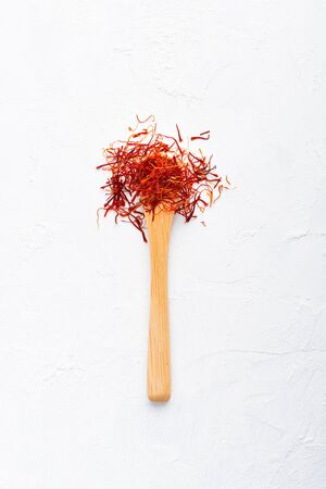 Spoonful of saffron on white wooden table top view flat lay.